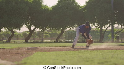 Front view of a mixed race male baseball player during a baseball game on a sunny day, catching a low ball in his mitt and throwing it, in slow motion