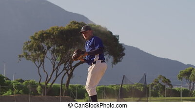 Front view of a mixed race male baseball player, during a baseball game on a sunny day, catching a high flying ball in his mitt and throwing it, in slow motion