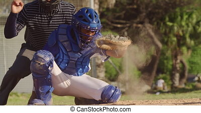 Front view of a mixed race male baseball player during a baseball game on a sunny day, playing in the catcher position, squatting and catching a ball, in slow motion