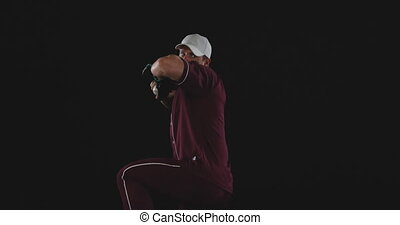 Front view of a Caucasian male baseball pitcher throwing a baseball, slow motion, on black background shot in the studio