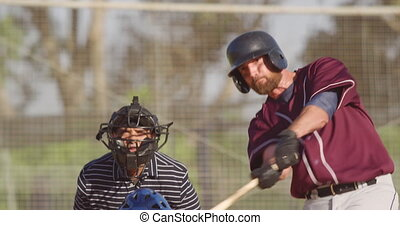 Baseball player hitting a ball during a match - Front view ...