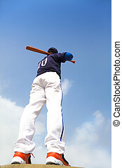 baseball player holding a bat  with blue sky