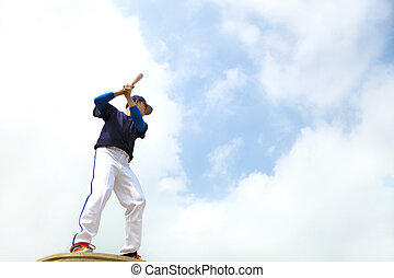 baseball player make a pose for hitting ball with blue sky