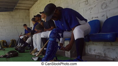 Side view of a mixed race male baseball player preparing to play in the catcher position before a game, sitting in a changing room, putting on leg pads, with his teammates talking in the background in slow motion