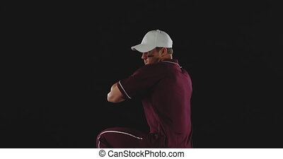 Side view of a Caucasian male baseball pitcher throwing a baseball, slow motion, on a black background shot in studio
