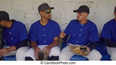 Front view of multi-ethnic group of male baseball players, preparing before a game, sitting in a changing room, two of them talking and fist bumping, in slow motion