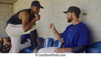 Baseball players discussing together - Side view of a mixed ...
