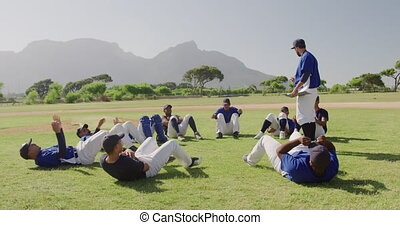 Side view of a Caucasian male baseball coach standing in a playing field instructing a multi-ethnic team of male baseball players, training before a game, working out doing sit-ups on a sunny day, in slow motion