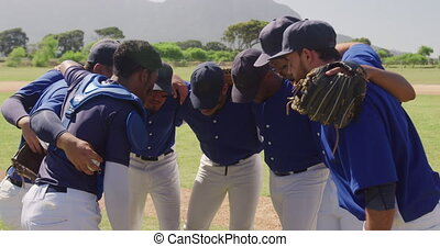 Side view of multi-ethnic team of male baseball players, preparing before a game, in a huddle on a baseball field, focusing on a sunny day, in slow motion