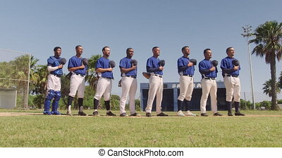 Front view of a multi-ethnic team of male baseball players, preparing before a game, standing in a row, holding their caps on their chests, listening to national anthem on a sunny day, in slow motion