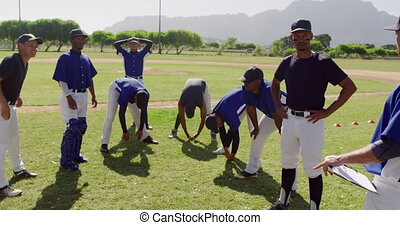 Front view of a multi-ethnic group of male baseball players, preparing for a game, standing on a playing field listening to their coach and resting after a training session a sunny day, in slow motion