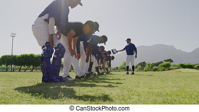 Side view close up of a Caucasian male baseball coach instructing a multi-ethnic team of male baseball players during a training session on a playing field on a sunny day, preparing before a game, bending forward and stretching, doing exercises, in slow motion