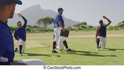 Side view of a Caucasian male baseball coach instructing a multi-ethnic team of male baseball players during a training session on a playing field on a sunny day, preparing before a game, kneeling down and stretching, doing exercises, in slow motion