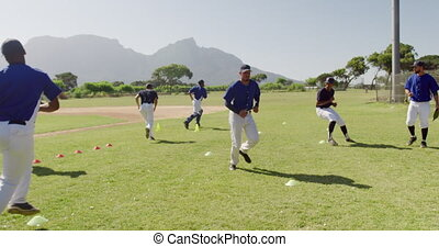 Front view of a multi-ethnic team of male baseball players, preparing before a game, working out and doing training exercises at a sports field on a sunny day, in slow motion