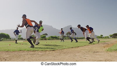 Low angle side view of a multi-ethnic group of male baseball players, training with their coach at a playing field, working out, doing short sprints and turning, on a sunny day, in slow motion