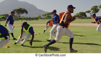 Side view close up of a multi-ethnic group of male baseball players, training with their coach at a playing field, working out, doing short sprints and turning, on a sunny day, in slow motion