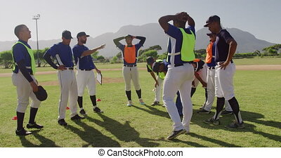 Side view of a multi-ethnic group of male baseball players and their coach, resting and talking during a training session at a playing field on a sunny day in slow motion