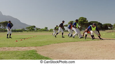 Side view of a multi-ethnic group of male baseball players, training with their coach at a playing field, working out, doing short sprints and turning, on a sunny day, in slow motion