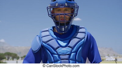 Front view of a Caucasian male baseball player, a catcher, wearing a protective vest, a helmet and a mitt, training at a sports field in slow motion