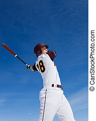 Baseball practice - A baseball player taking a swing during...