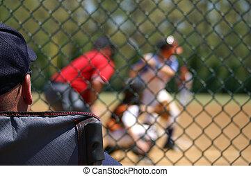 Baseball Spectator - Baseball fan watching boy at bat during...