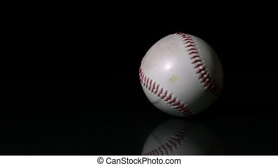 Baseball spinning on black surface in slow motion