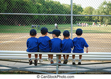 Baseball team on the bench - five little boys sit on the...