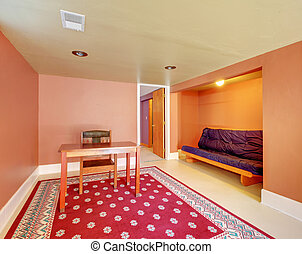Basement room with desk and sofa in orange.