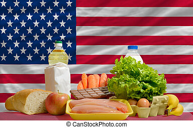 complete national flag of us covers whole frame, waved, crunched and very natural looking. In front plan are fundamental food ingredients for consumers, symbolizing consumerism an human needs
