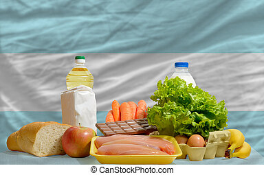 complete national flag of argentina covers whole frame, waved, crunched and very natural looking. In front plan are fundamental food ingredients for consumers, symbolizing consumerism an human needs