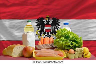 complete national flag of austria covers whole frame, waved, crunched and very natural looking. In front plan are fundamental food ingredients for consumers, symbolizing consumerism an human needs