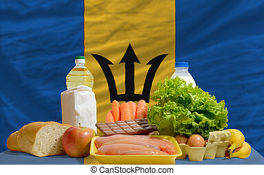 complete national flag of barbadian covers whole frame, waved, crunched and very natural looking. In front plan are fundamental food ingredients for consumers, symbolizing consumerism an human needs