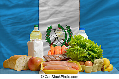 complete national flag of guatemala covers whole frame, waved, crunched and very natural looking. In front plan are fundamental food ingredients for consumers, symbolizing consumerism an human needs