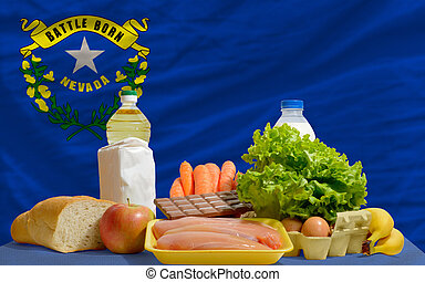 complete american state flag of nevada covers whole frame, waved, crunched and very natural looking. In front plan are fundamental food ingredients for consumers, symbolizing consumerism an human needs