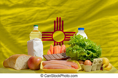 complete american state flag of new mexico covers whole frame, waved, crunched and very natural looking. In front plan are fundamental food ingredients for consumers, symbolizing consumerism an human needs