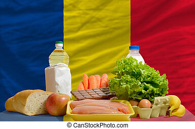 complete national flag of romania covers whole frame, waved, crunched and very natural looking. In front plan are fundamental food ingredients for consumers, symbolizing consumerism an human needs