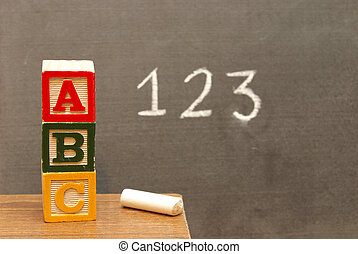 Alphabet blocks and numbers wrote on the chalkboard for learning the basics of the english language.