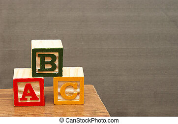 Basic Learning - Alphabet blocks in front of the chalkboard...