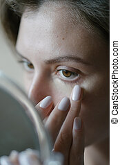 Basic make-up the morning before work. A young woman applies cosmetics and looks into the hand mirror. Close-up