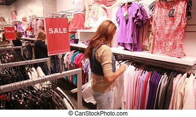 Stylish girl choosing basic pieces of clothes for her wardrobe