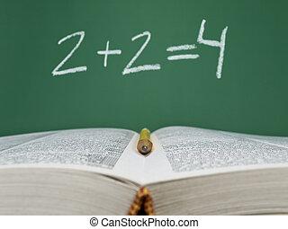 Basic sum - 2 + 2 = 4 written on a chalkboard with an open...