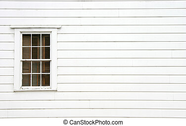 A window on the side of an old house.