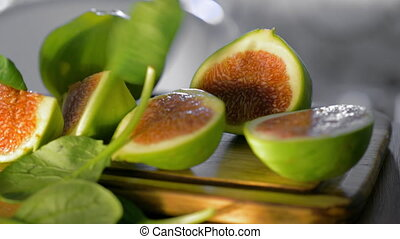 Basil leaves falling on cut green figs - Close-up shot of...