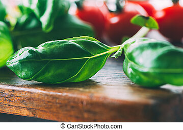 Basil leaves on wooden cutting board with cherry tomatoes