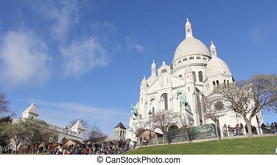 Basilica Sacre-Coeur of Paris with light in the foreground. Blue sky and trees.