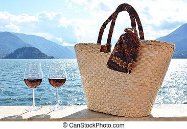 Basket bag and wineglasses. Varenna town at the lake Como,...