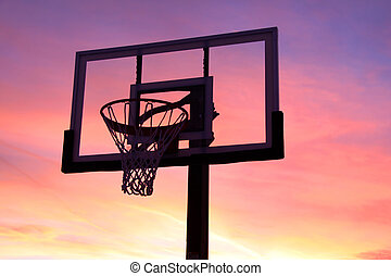 Basket ball hoop against bright orange sky background