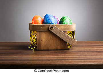 Basket, colored easter eggs on table, gray background