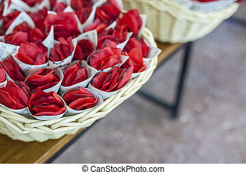 Basket full of cornets filled with red rose for wedding
