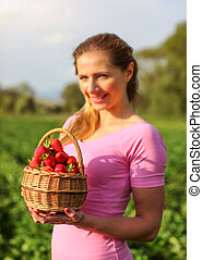 Basket full of red ripe strawberries, blurred young woman holding it, and strawberry fields in background.